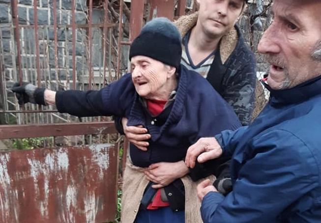 Через багнюку в Мукачеві не могли перенести до машини немічну бабусю (фото)